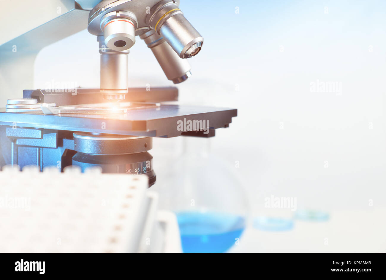 Scientific background with closeup on light microscope and laboratory out of focus. This image is toned. Shallow - Stock Image