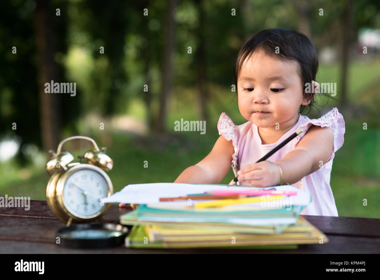 little baby toddler drawing using left hand at park. left handed concept - Stock Image