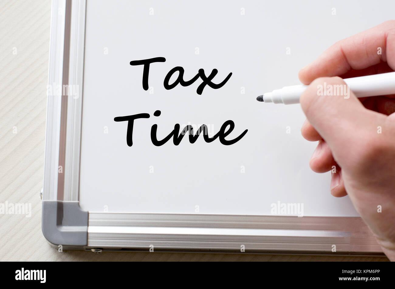 Tax time written on whiteboard - Stock Image