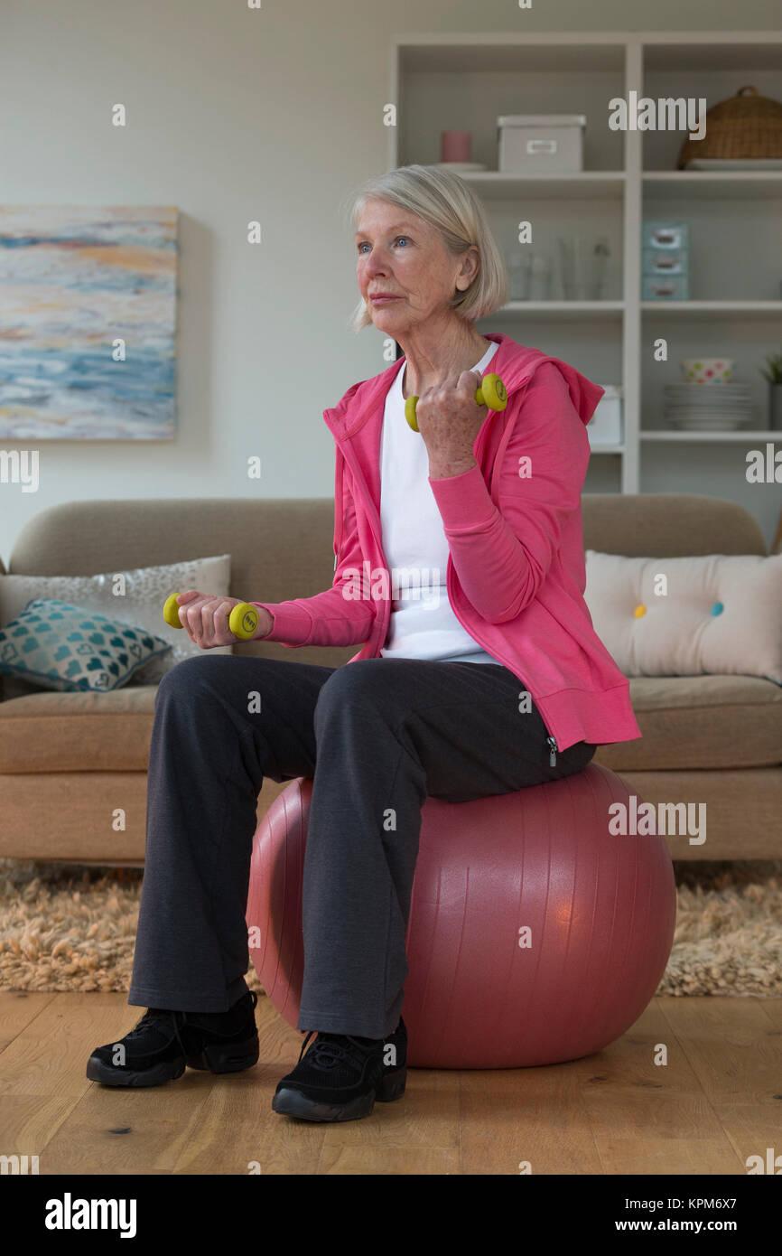 Senior lady exercising at home - Stock Image