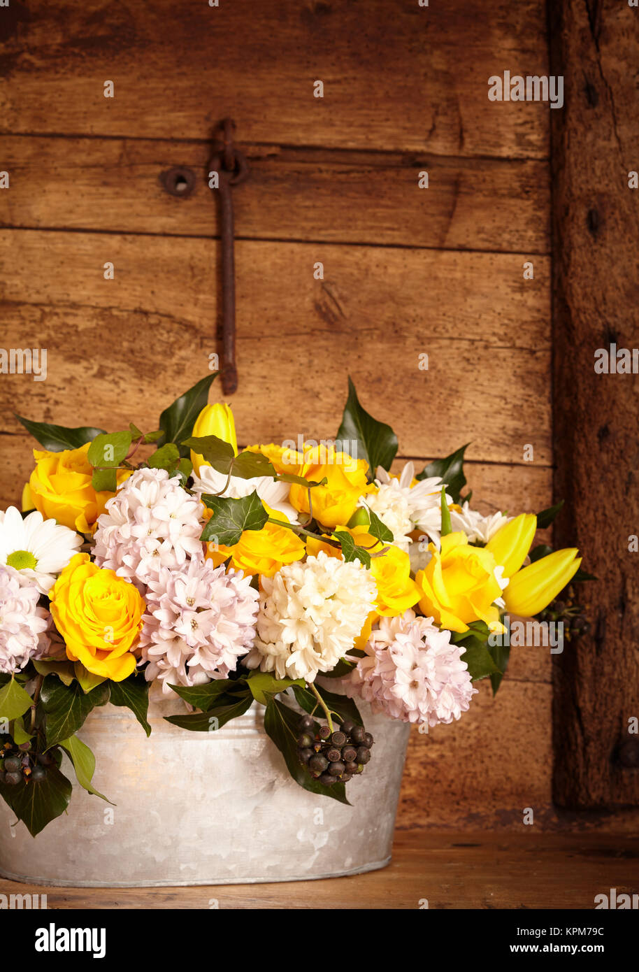 Group of beautiful white and yellow flowers in old galvanized steel bucket over rustic interior background - Stock Image