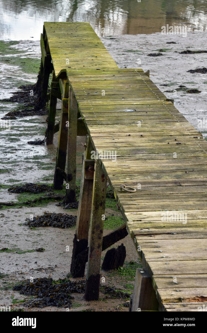 a rickety old wooden boardwalk or plank jetty on the river medina, isle of wight between nnewport and cowes. Slippery - Stock Image