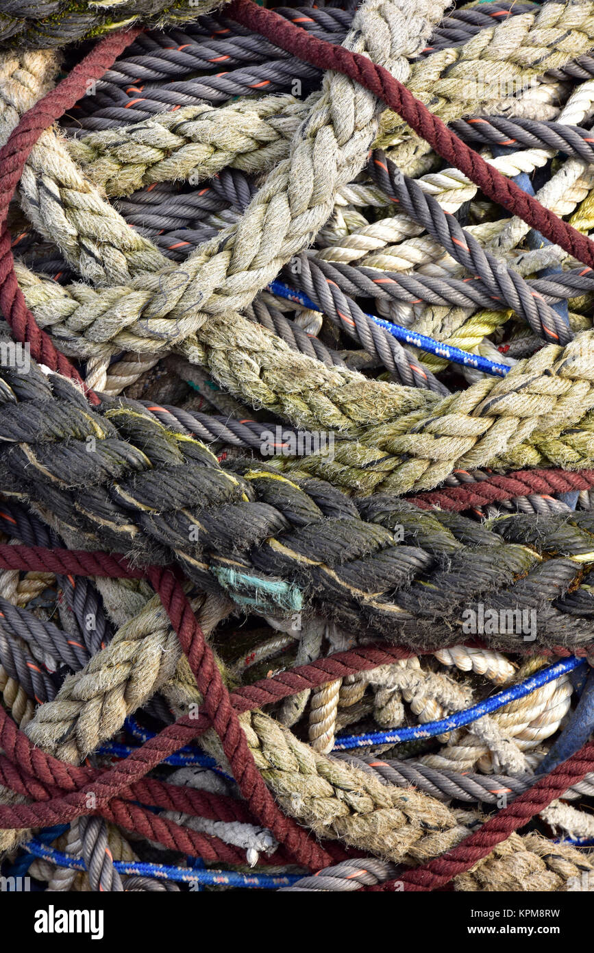 A tangle of various and differently sized and shaped colourful ropes and wires in a big mess and knotted together. - Stock Image