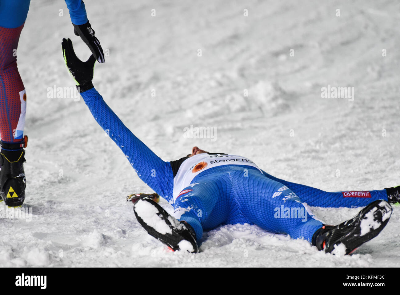 Italy's Federico Pellegrino (lying on snow) shakes hands with Russia's Sergey Ustiugov after winning the - Stock Image