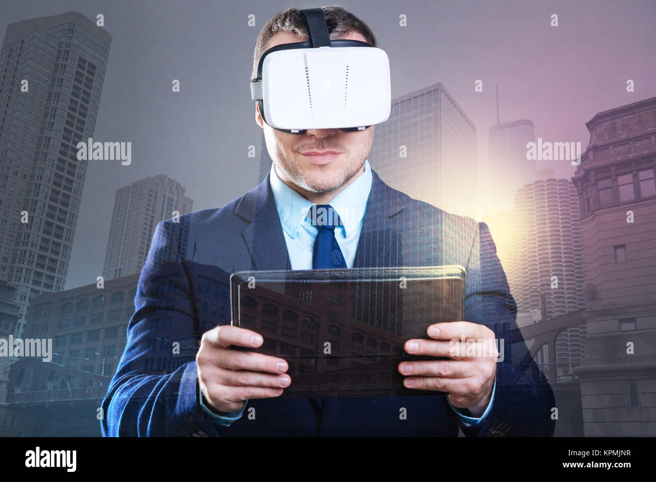 Successful young man working with VR headset and tablet computer - Stock Image