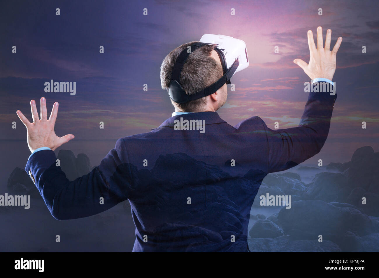 Turned back businessman wearing virtual reality goggles touching landscape - Stock Image