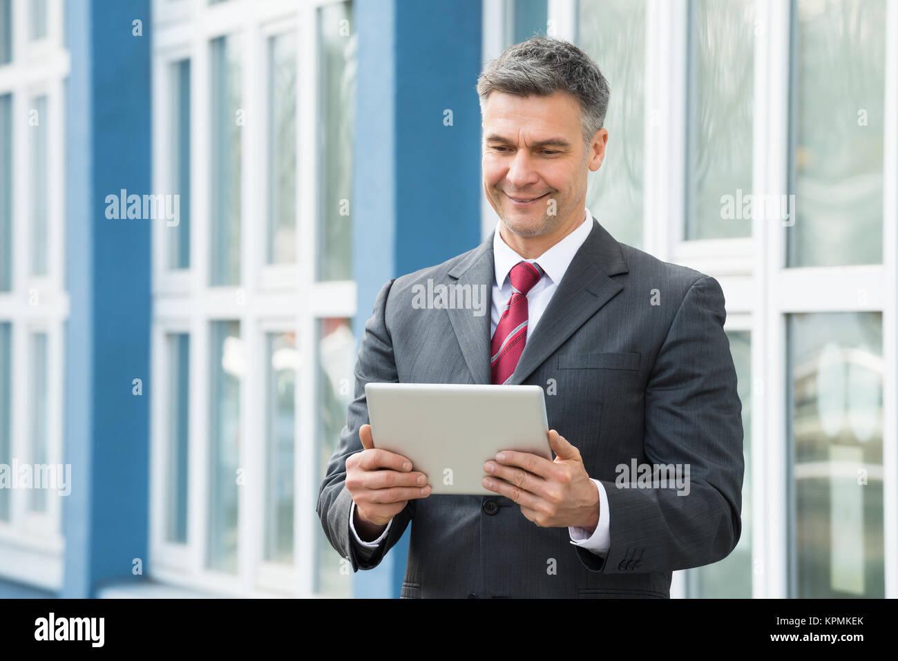 Businessman Holding Digital Tablet - Stock Image