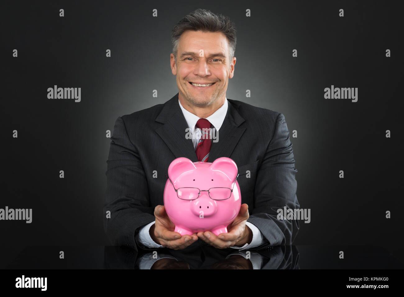 Businessman Sitting And Holding Piggybank Stock Photo