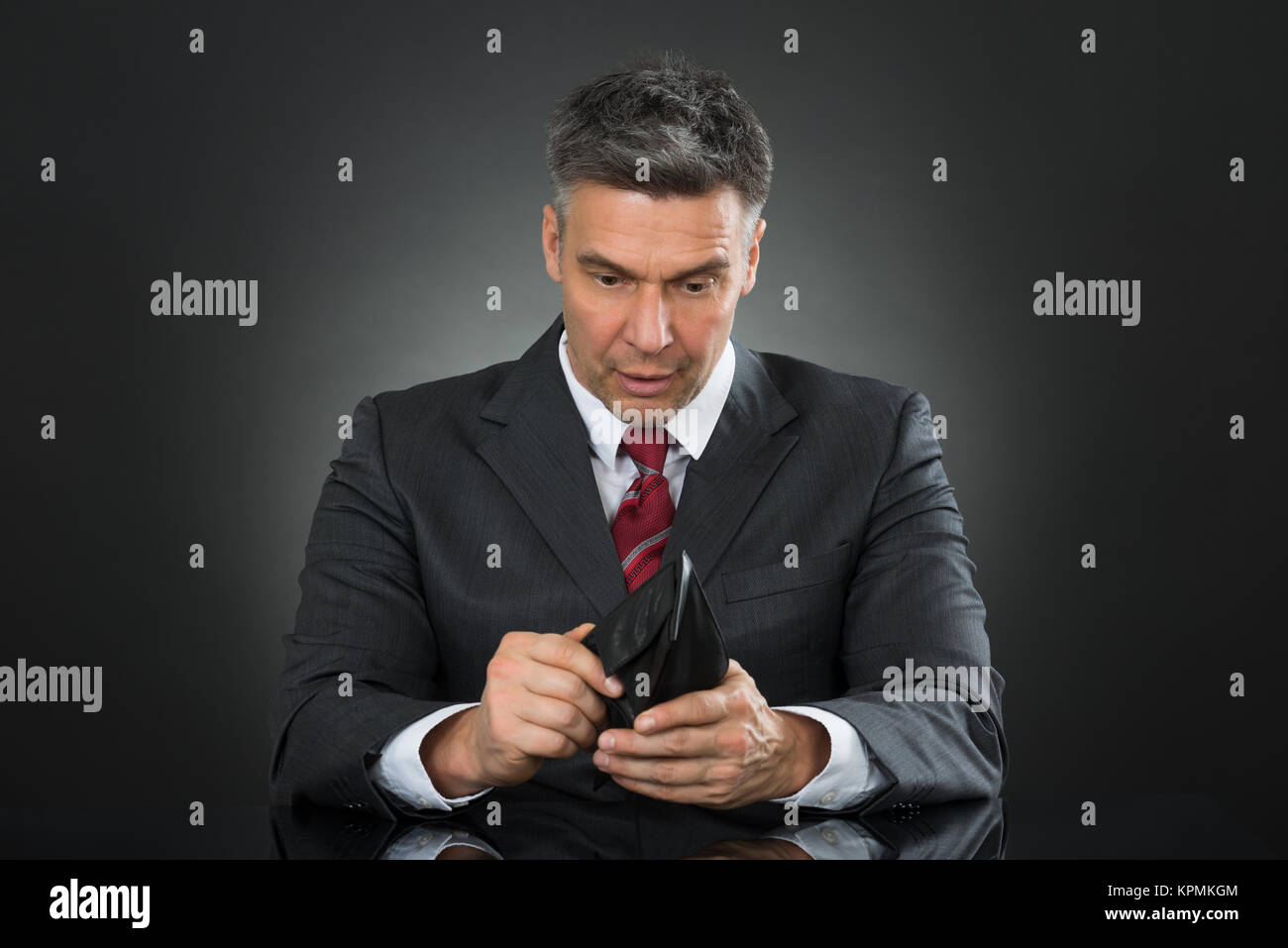 Businessman With Empty Wallet Sitting At Desk - Stock Image