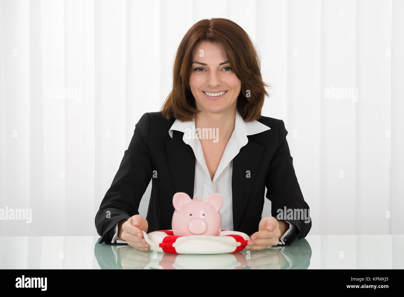 Businesswoman Sheltering Piggybank With Lifebelt - Stock Image