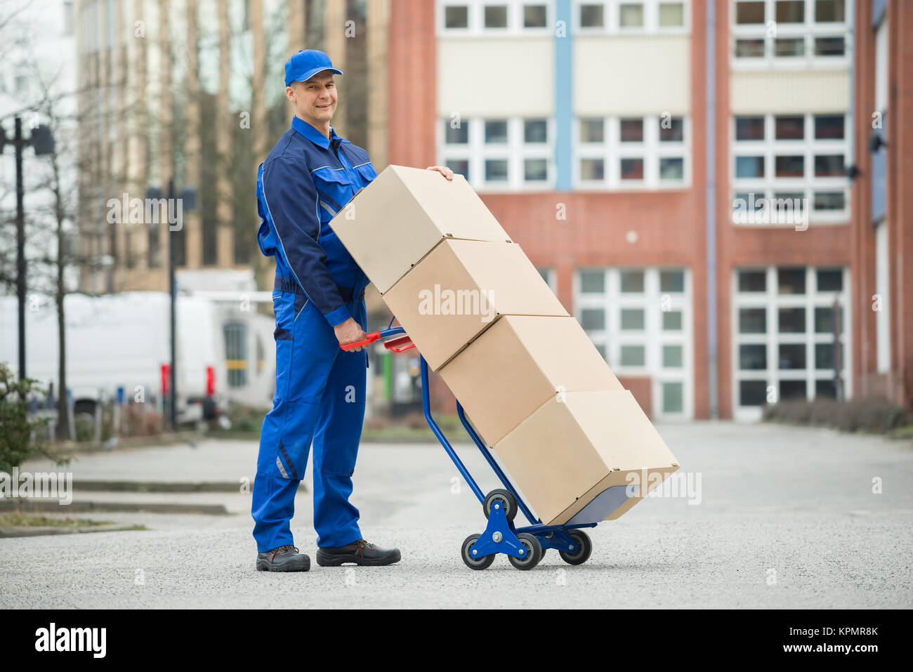 Deliveryman Holding Trolley Loaded With Cardboard Boxes - Stock Image