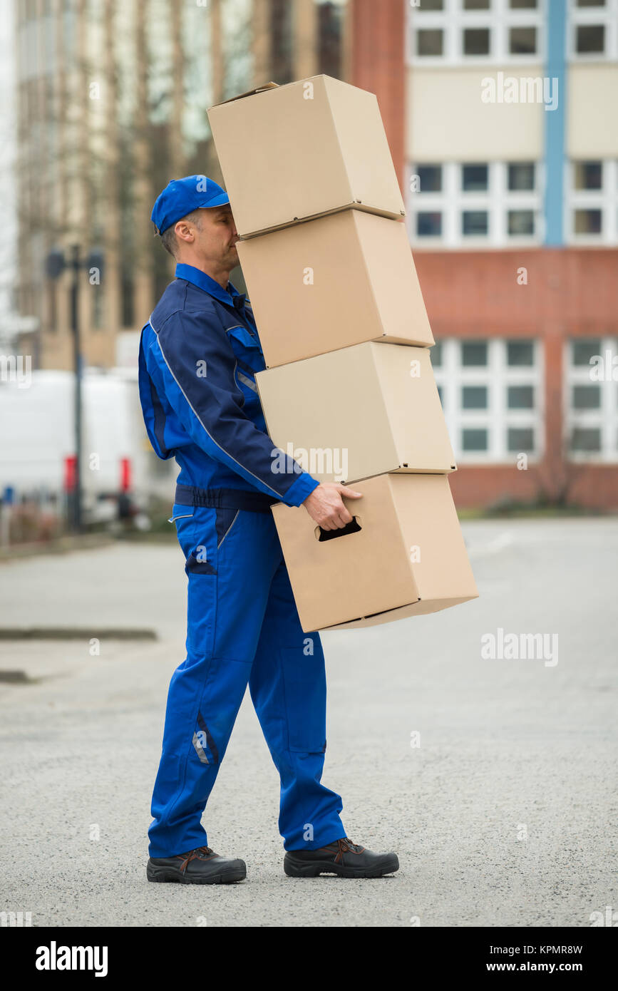 Delivery Man Balancing Stack Of Boxes - Stock Image