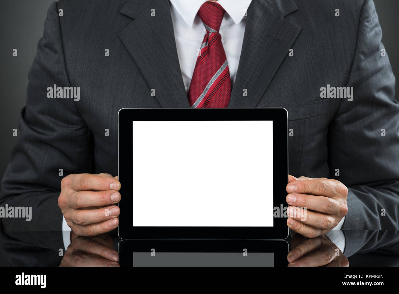 Businessman Showing Tablet With Blank Screen At Desk - Stock Image