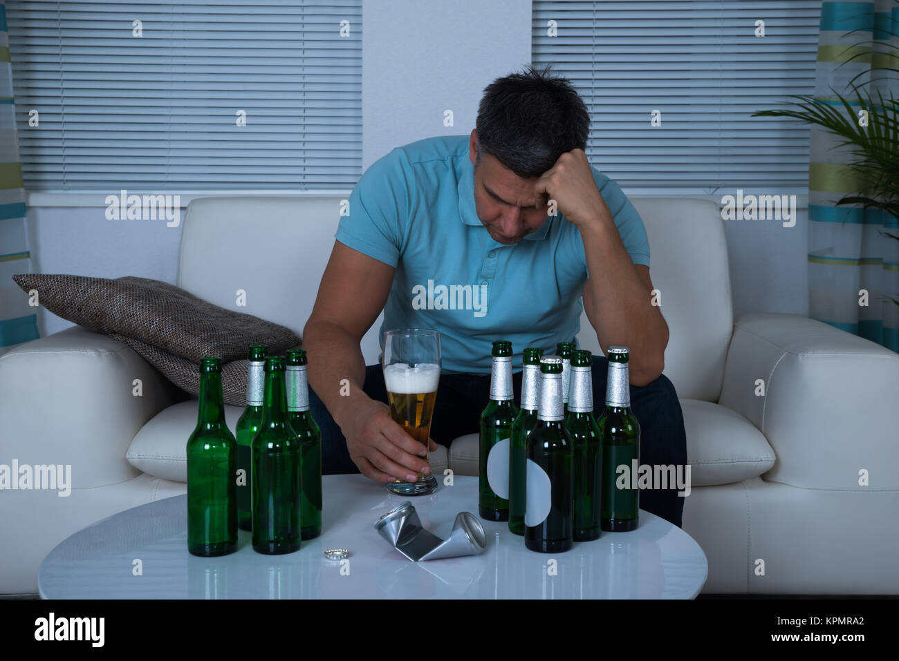 Man Sitting On Sofa In Front Of Beer During Night Stock Photo