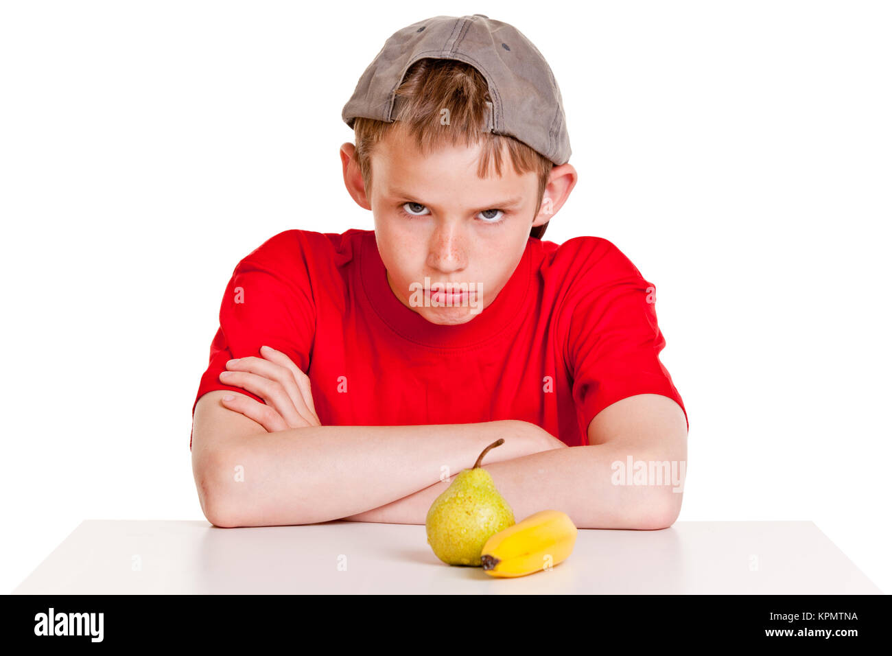 Belligerent young boy with fruit - Stock Image