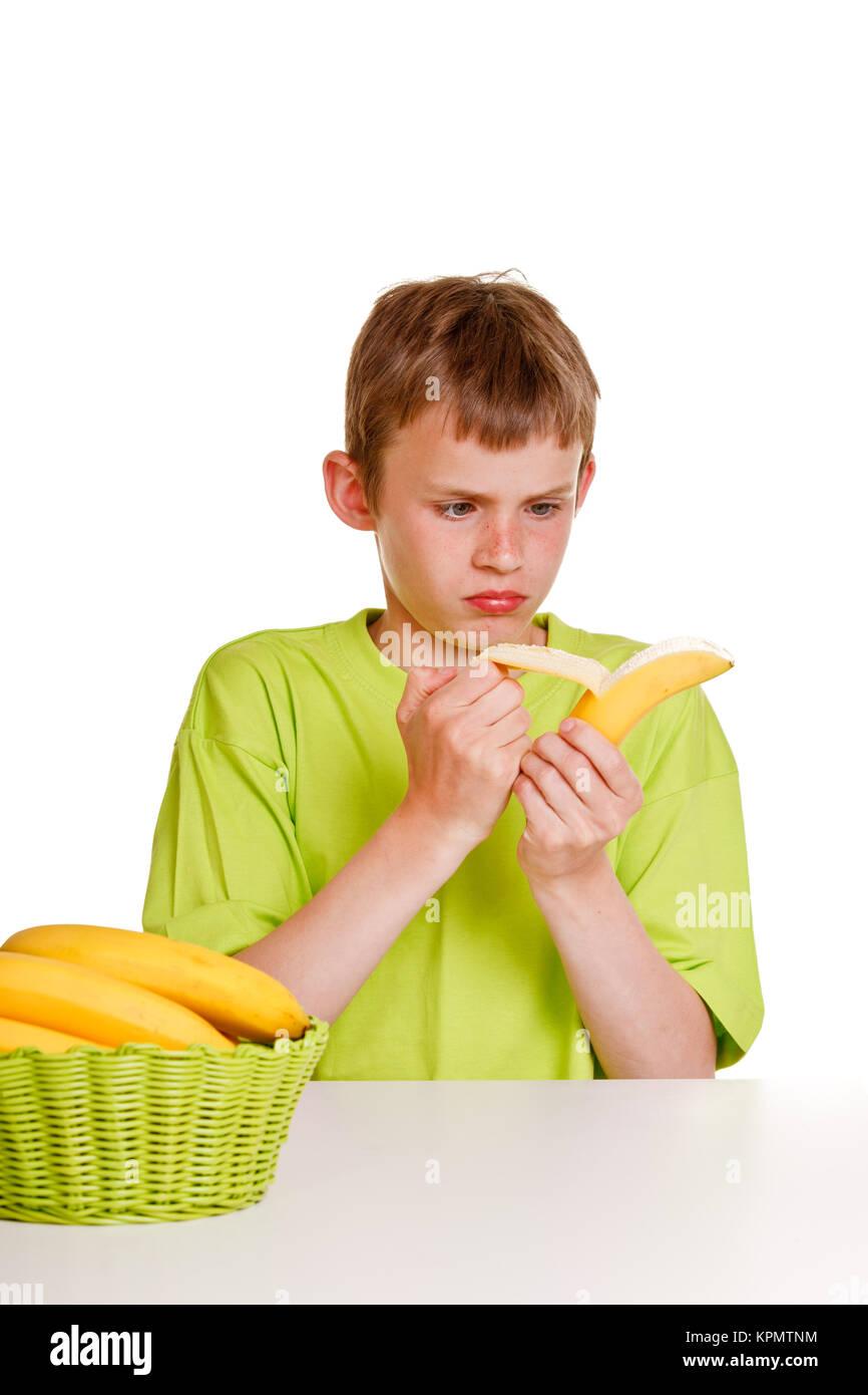 Young boy peeling a banana with distaste - Stock Image
