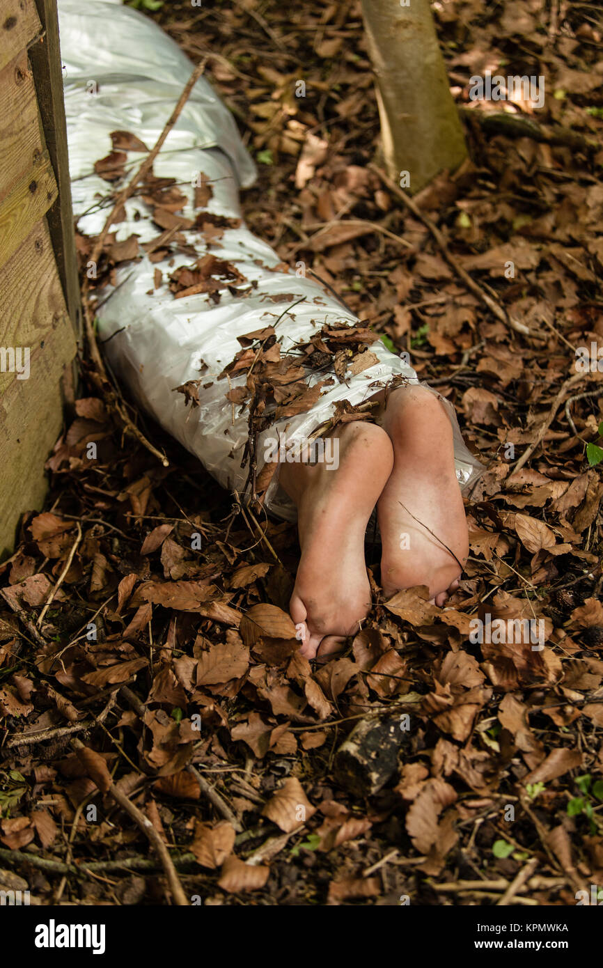 Wrapped barefoot corpse lying in the woods - Stock Image