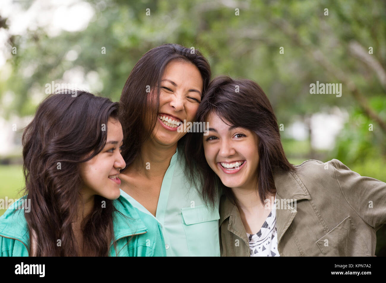 Asian mother laughing and huging her children. - Stock Image
