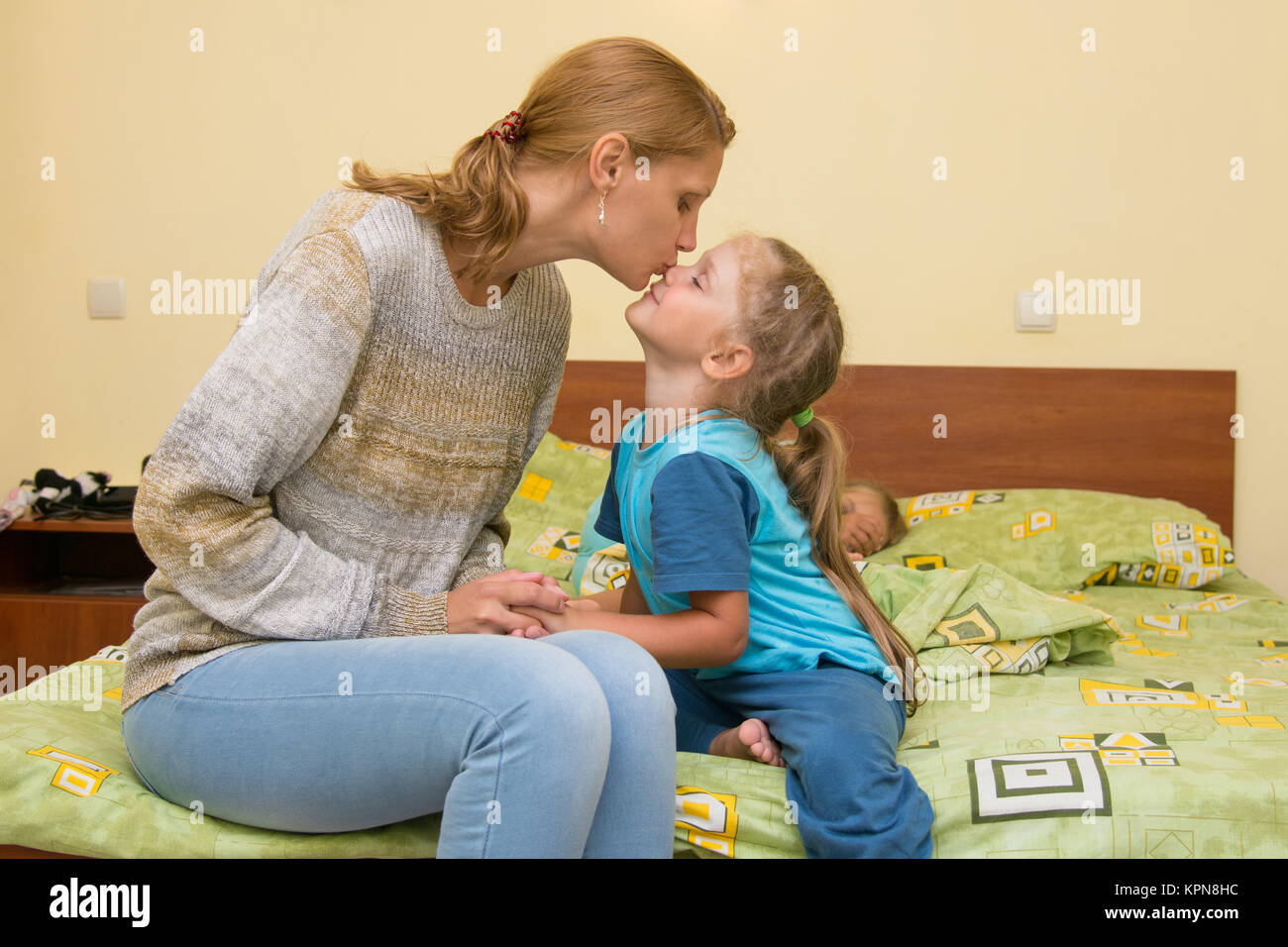 Mum kisses a daughter before a dream, sitting on the bed in the room - Stock Image