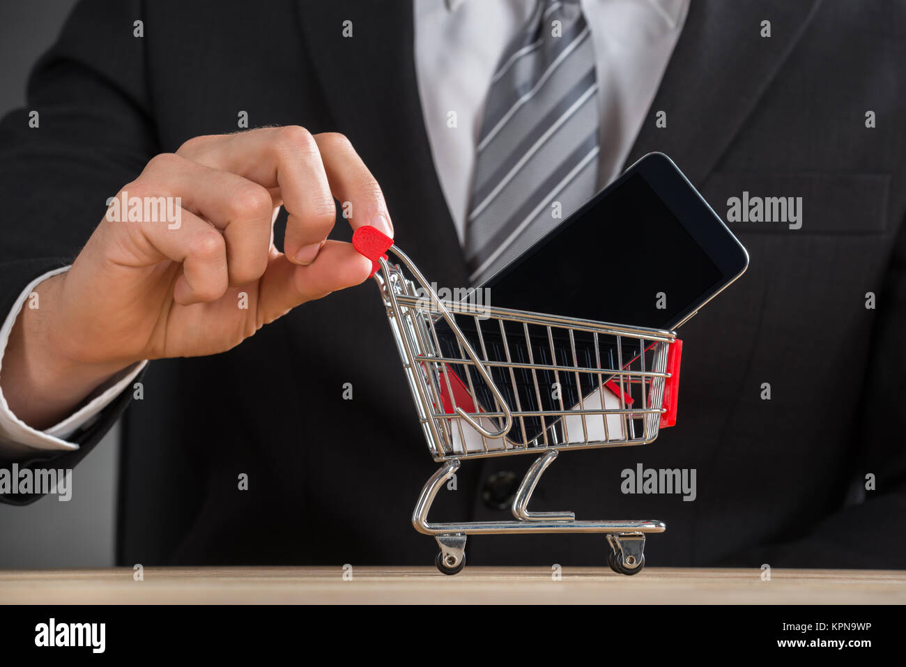 Businessman Holding Shopping Trolley With Mobile Phone - Stock Image