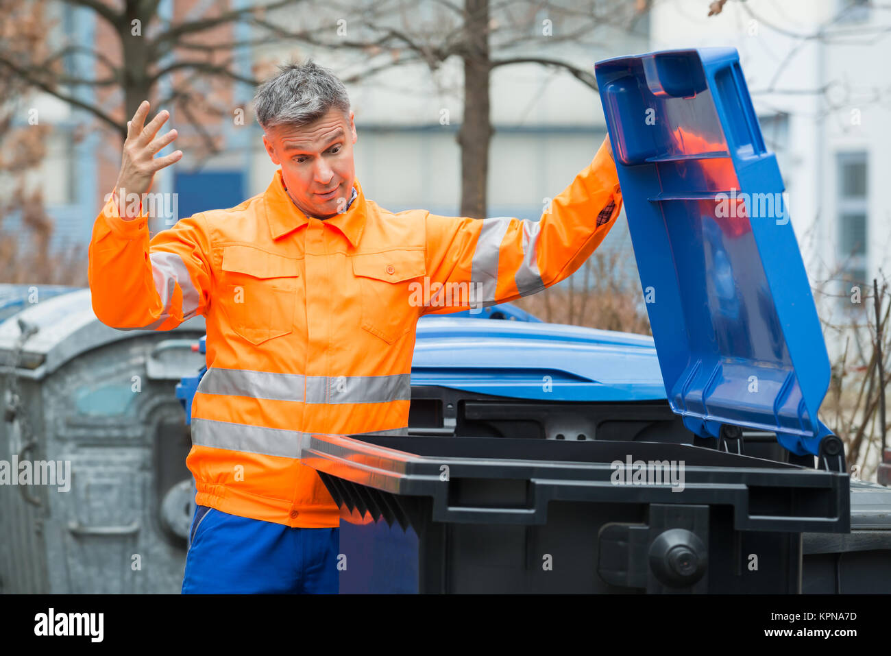 Street Cleaner Looking In Dustbin - Stock Image