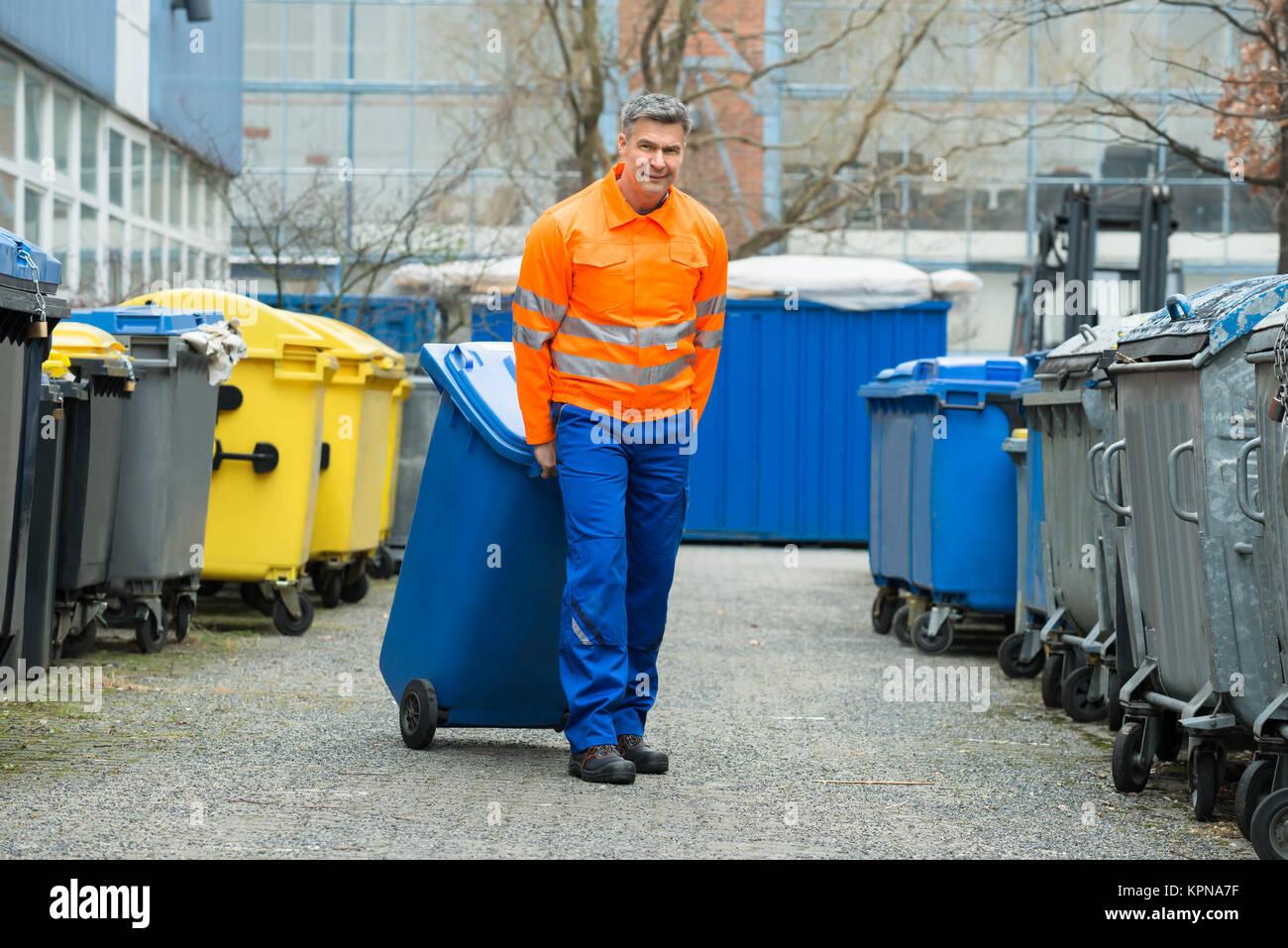 Male Worker Walking With Dustbin On Street - Stock Image