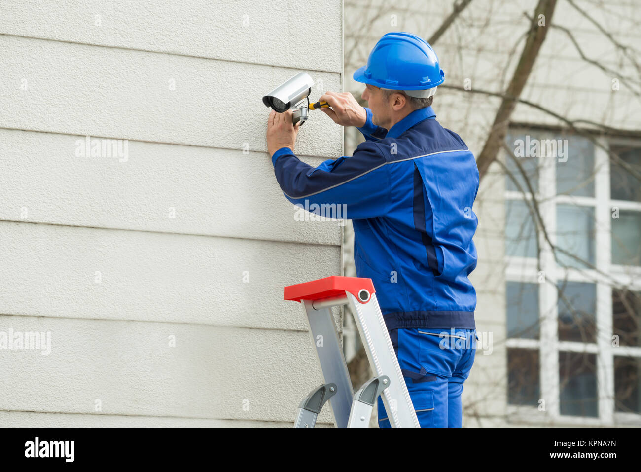 Male Technician Standing On Stepladder Fitting CCTV Camera - Stock Image