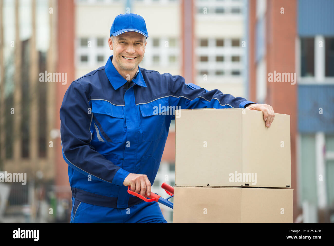 Deliveryman With Trolley Loaded With Cardboard Boxes - Stock Image