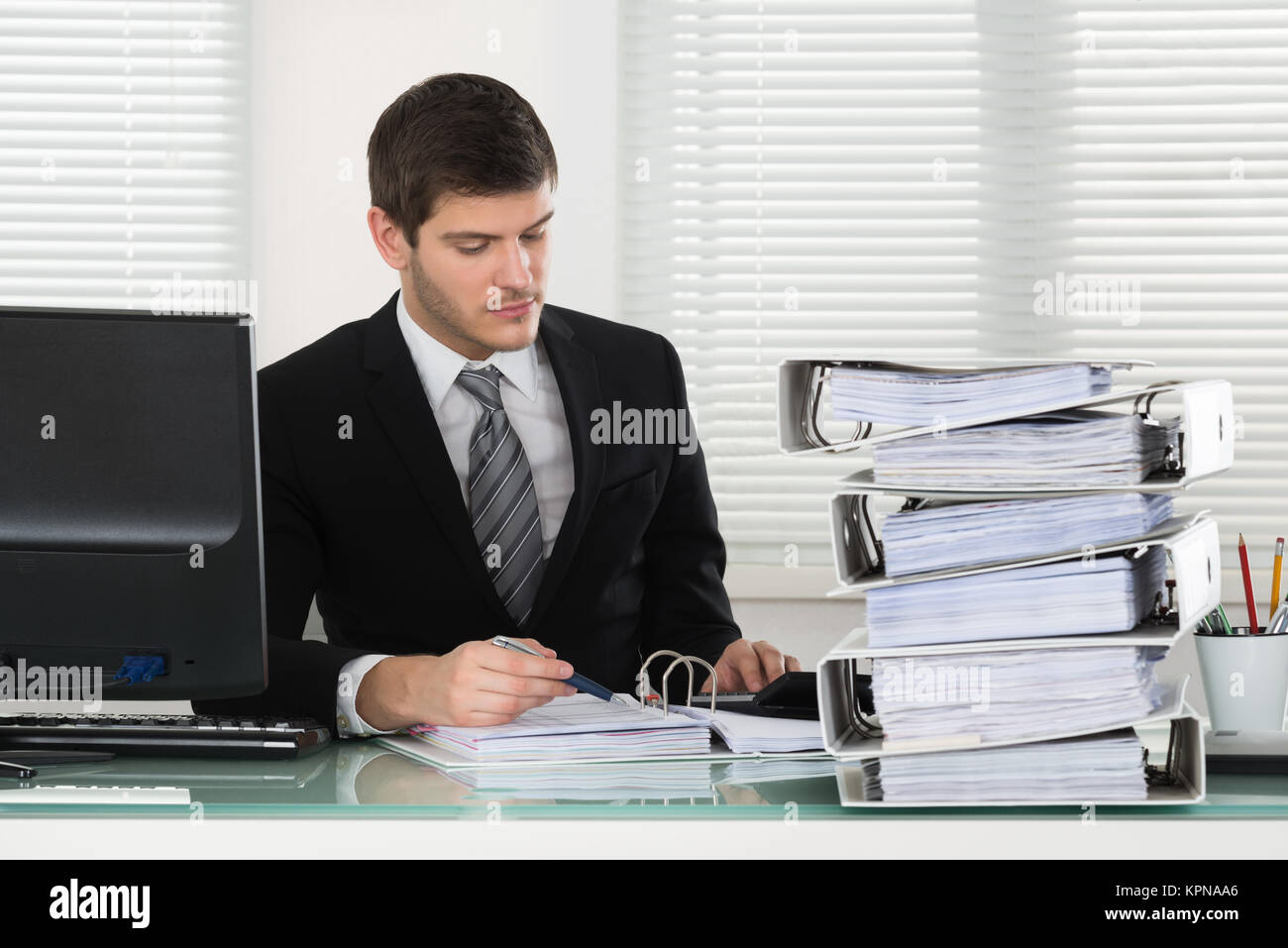 Businessman Calculating Invoice Stock Photo