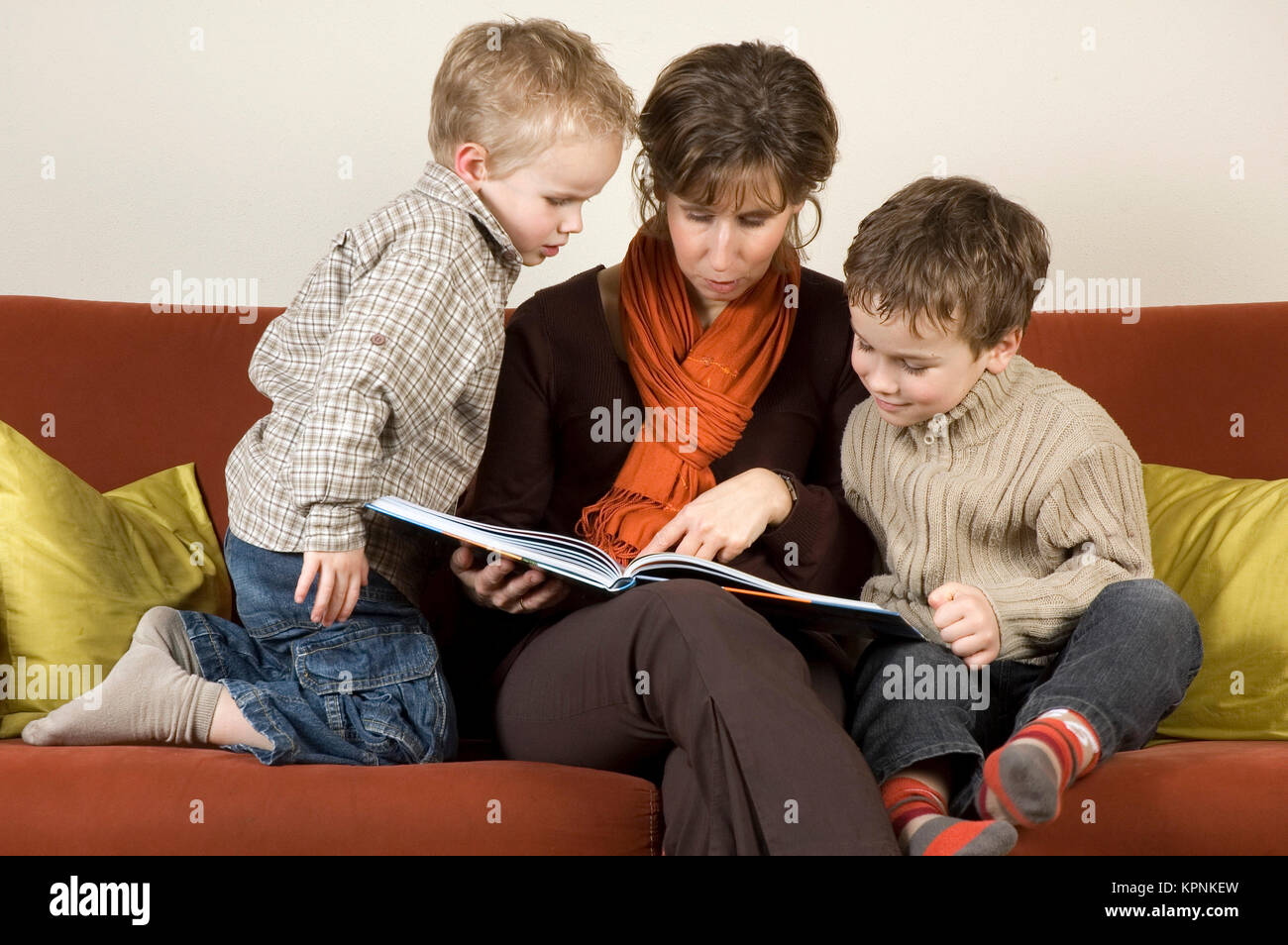 Mother And Two Sons Reading A Book 1 - Stock Image