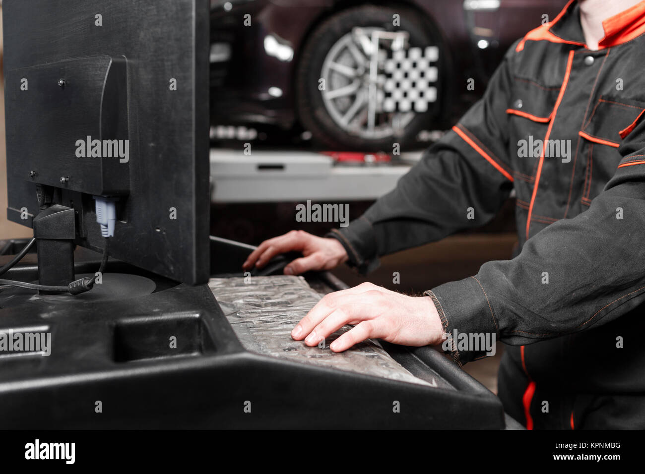 auto mechanic performs diagnostics and configuration on the computer . Wheel alignment equipment on a car wheel - Stock Image