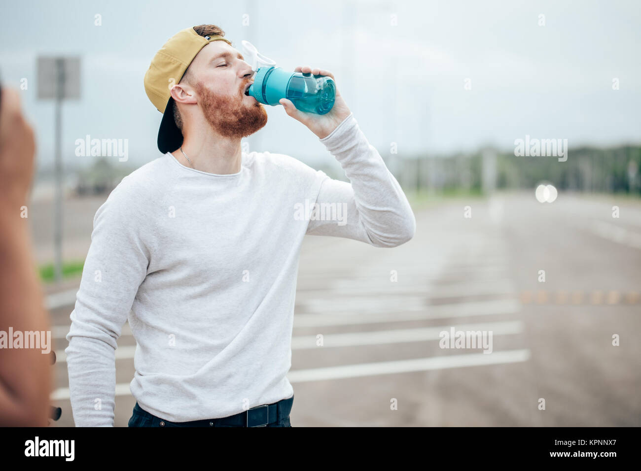 Cyclist drinking water over blue sky on road - Stock Image