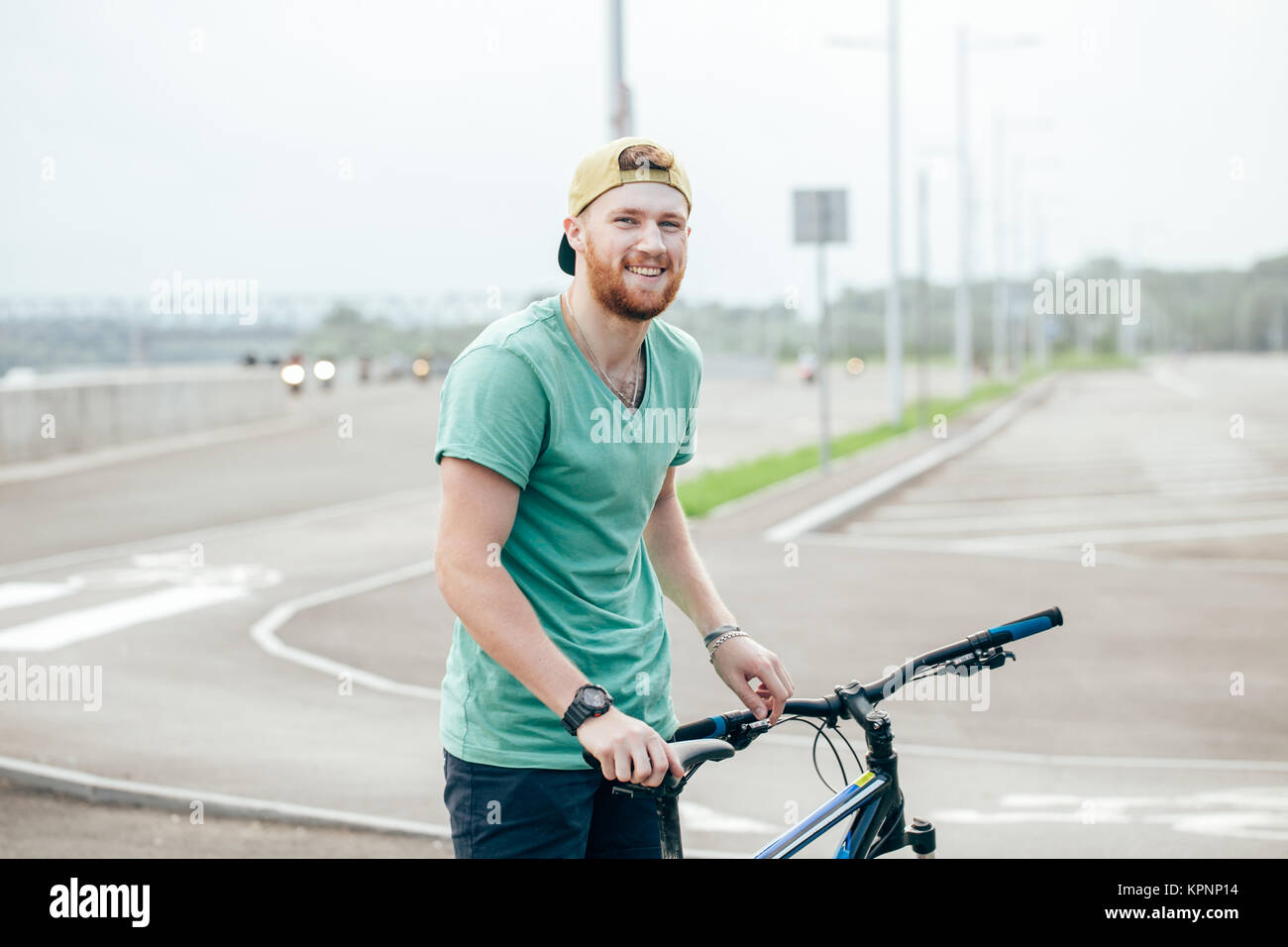 Man riding a bicycle on a road - Stock Image
