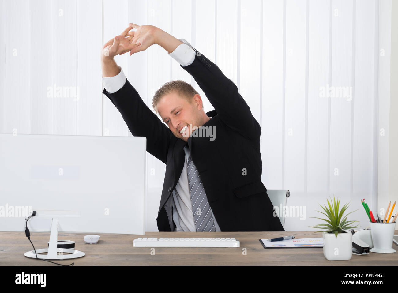 Businessman Stretching In Office - Stock Image