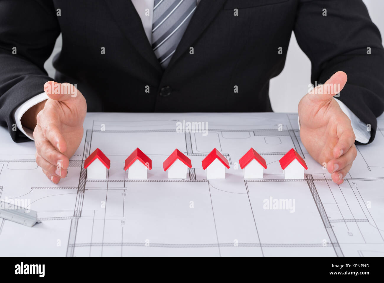 Architect Hand Protecting House Models - Stock Image