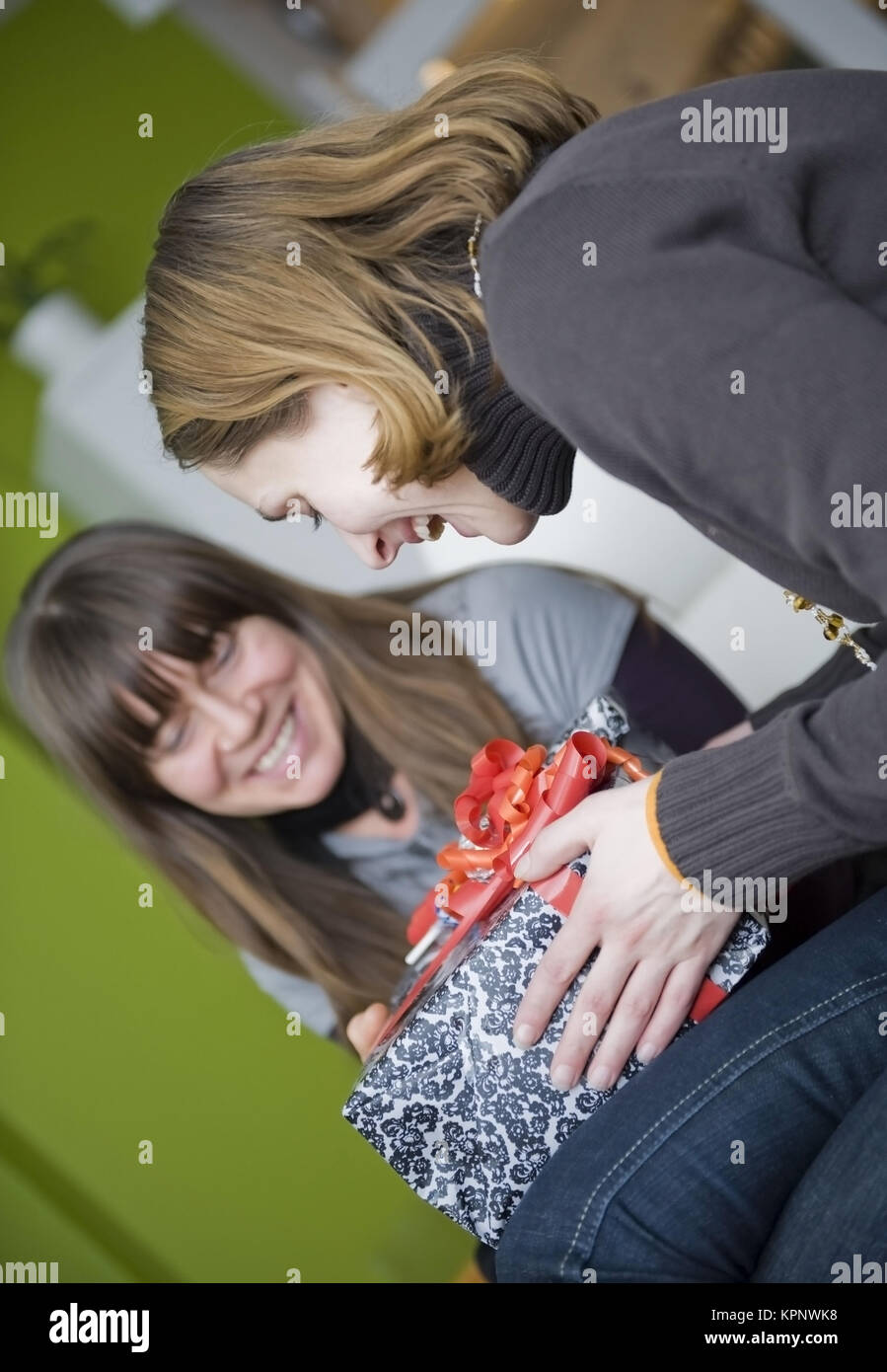 Model release , Zwei Freundinnen beim Geschenk auspacken - girl friends with present Stock Photo
