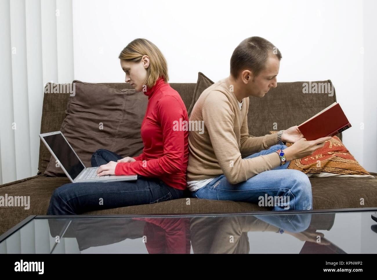 Model release , Frau arbeitet am Computer, Mann liest ein Buch - woman using laptop, man reading a book Stock Photo
