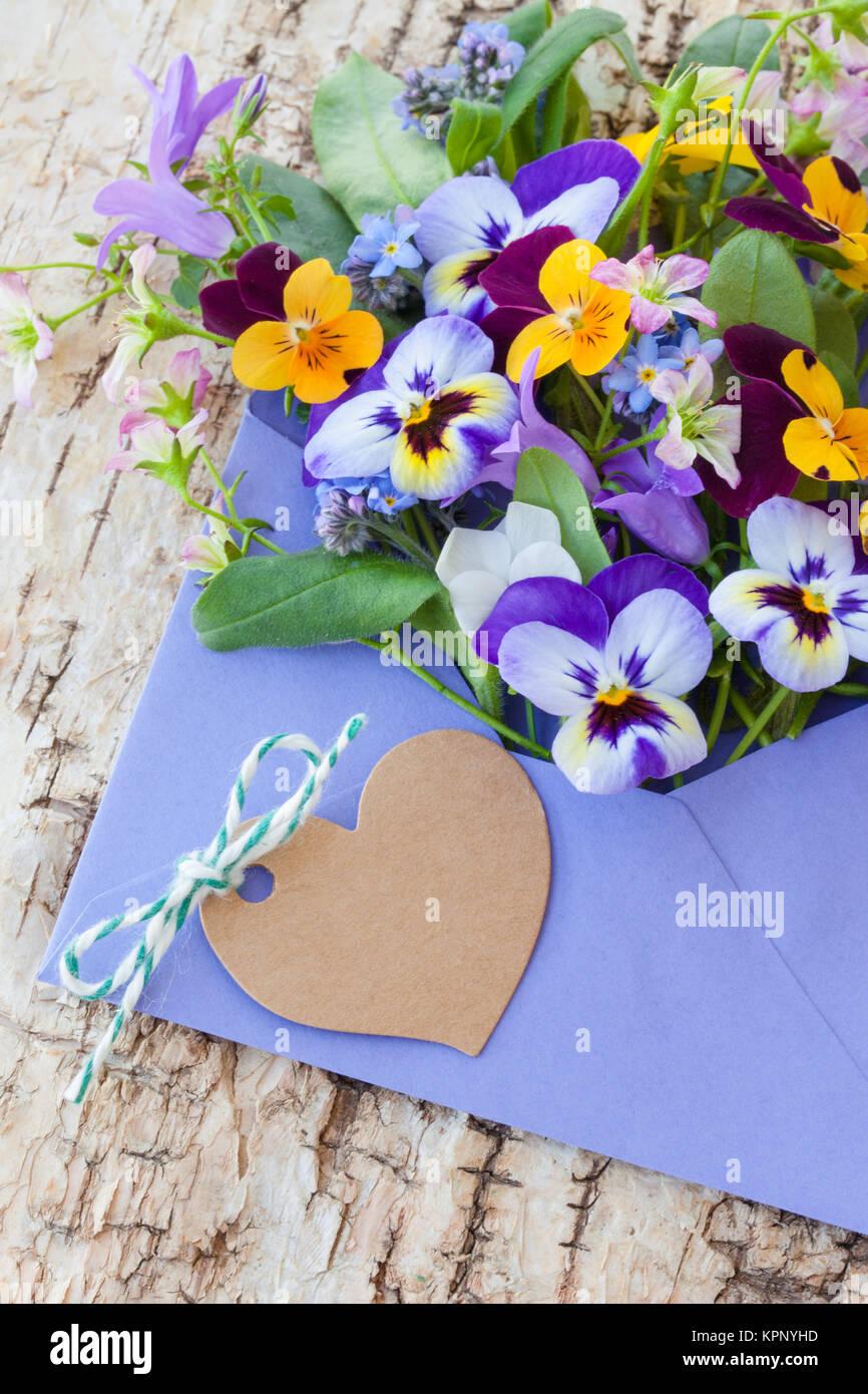 Bunter Strauss Fruehlingsblumen in kleinem Briefumschlag - Stock Image
