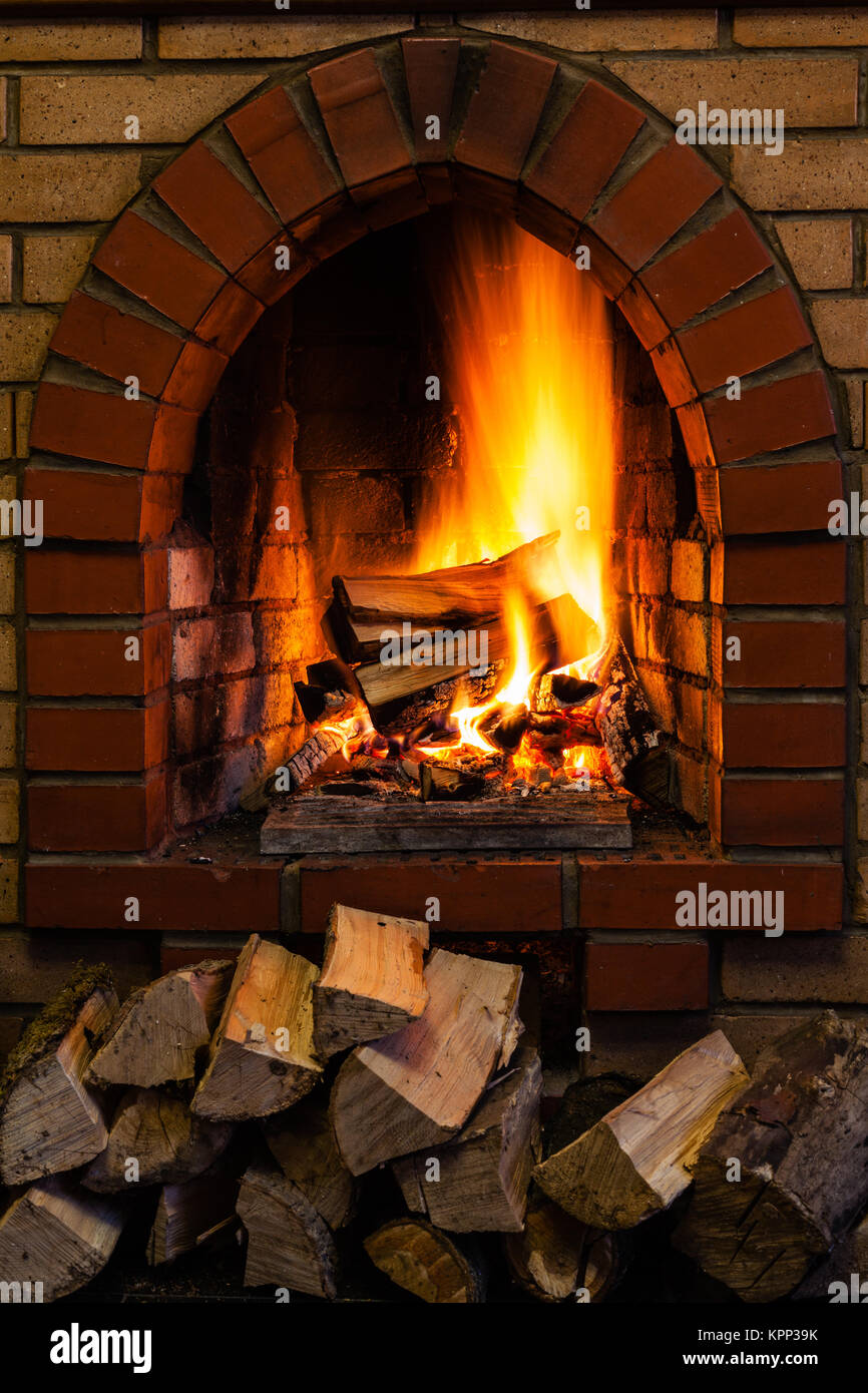 Wood Stack And Logs Burning In Brick Fireplace Stock Photo