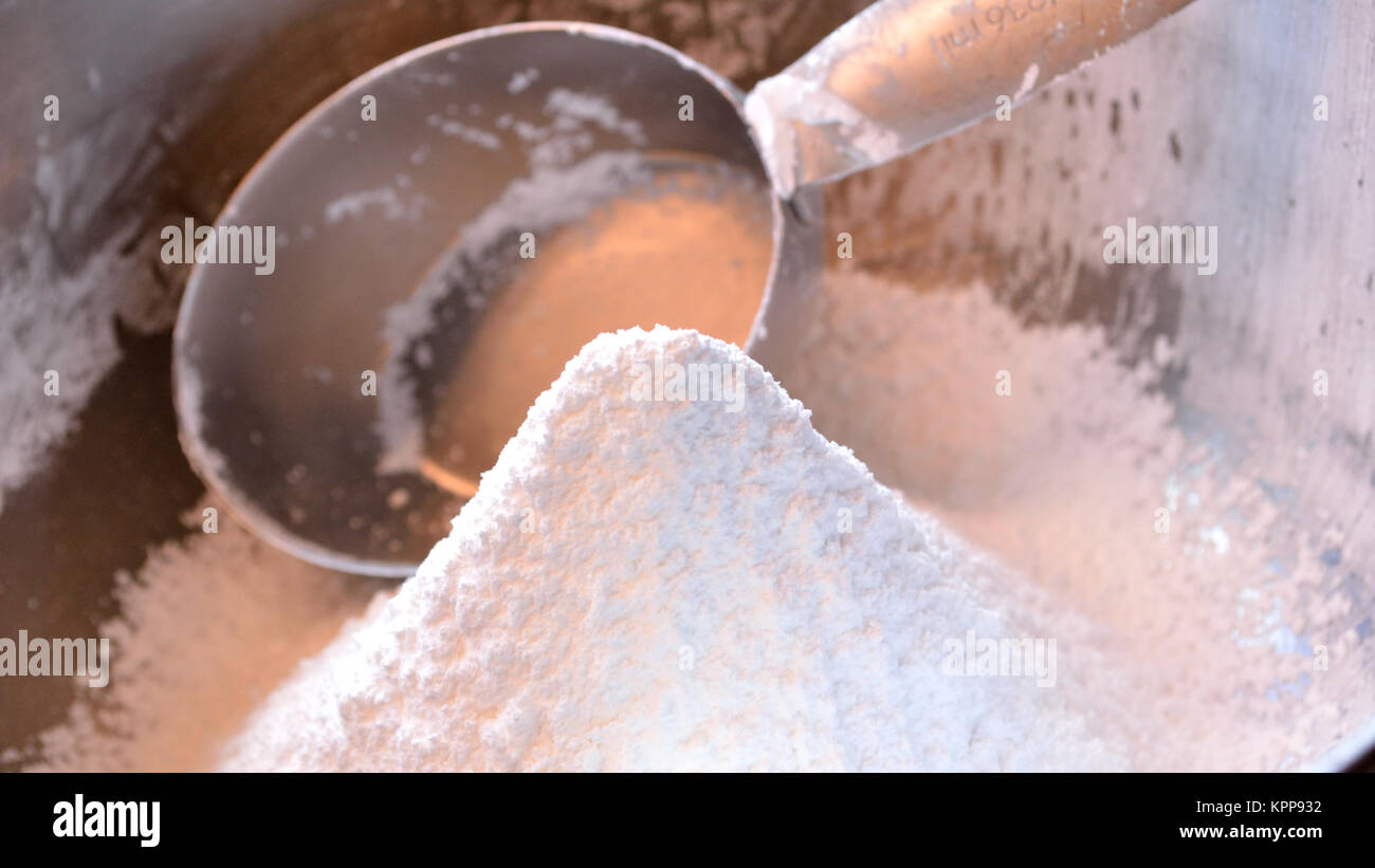 Confectioner's sugar widescreen with measuing cup - Stock Image