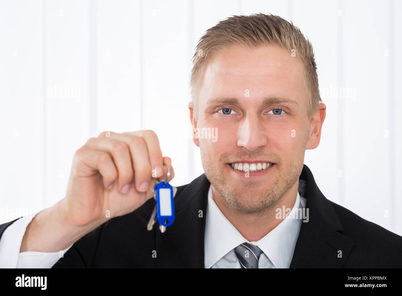 Businessman Holding House Keys In Office - Stock Image