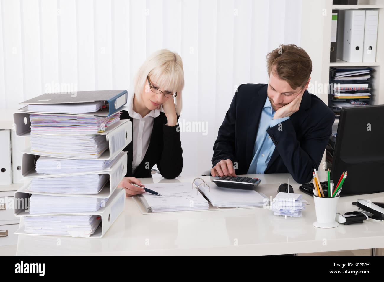 Businesspeople Calculating Invoices - Stock Image