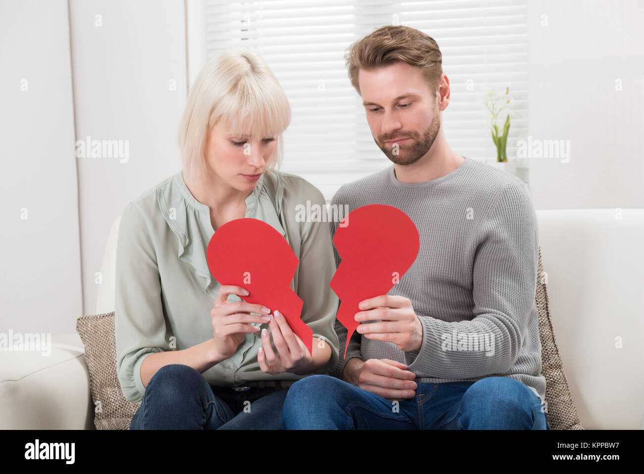Couple Holding Red Broken Heart - Stock Image