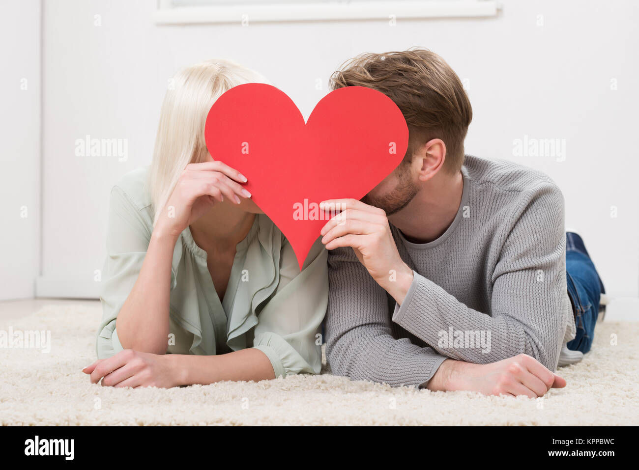 Couple Kissing Behind Heart Shape - Stock Image