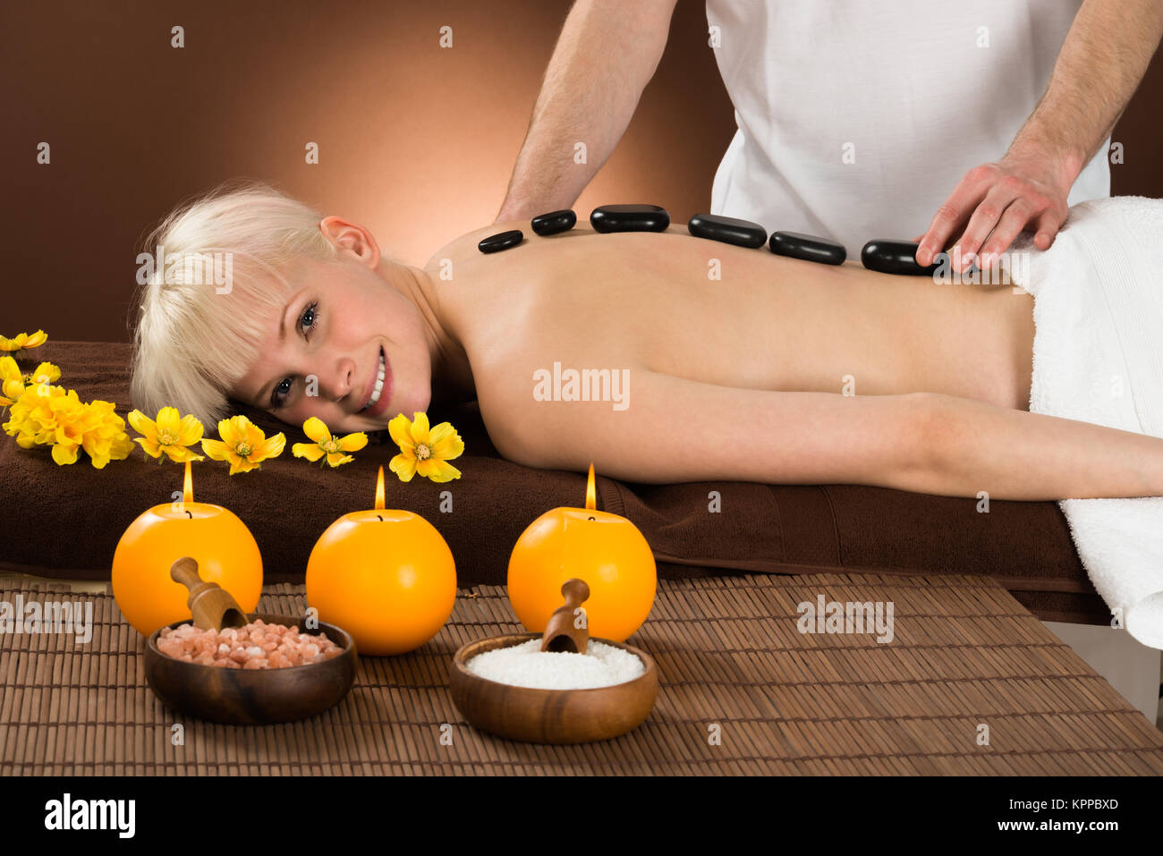 Young Woman Receiving Hot Stone Therapy - Stock Image