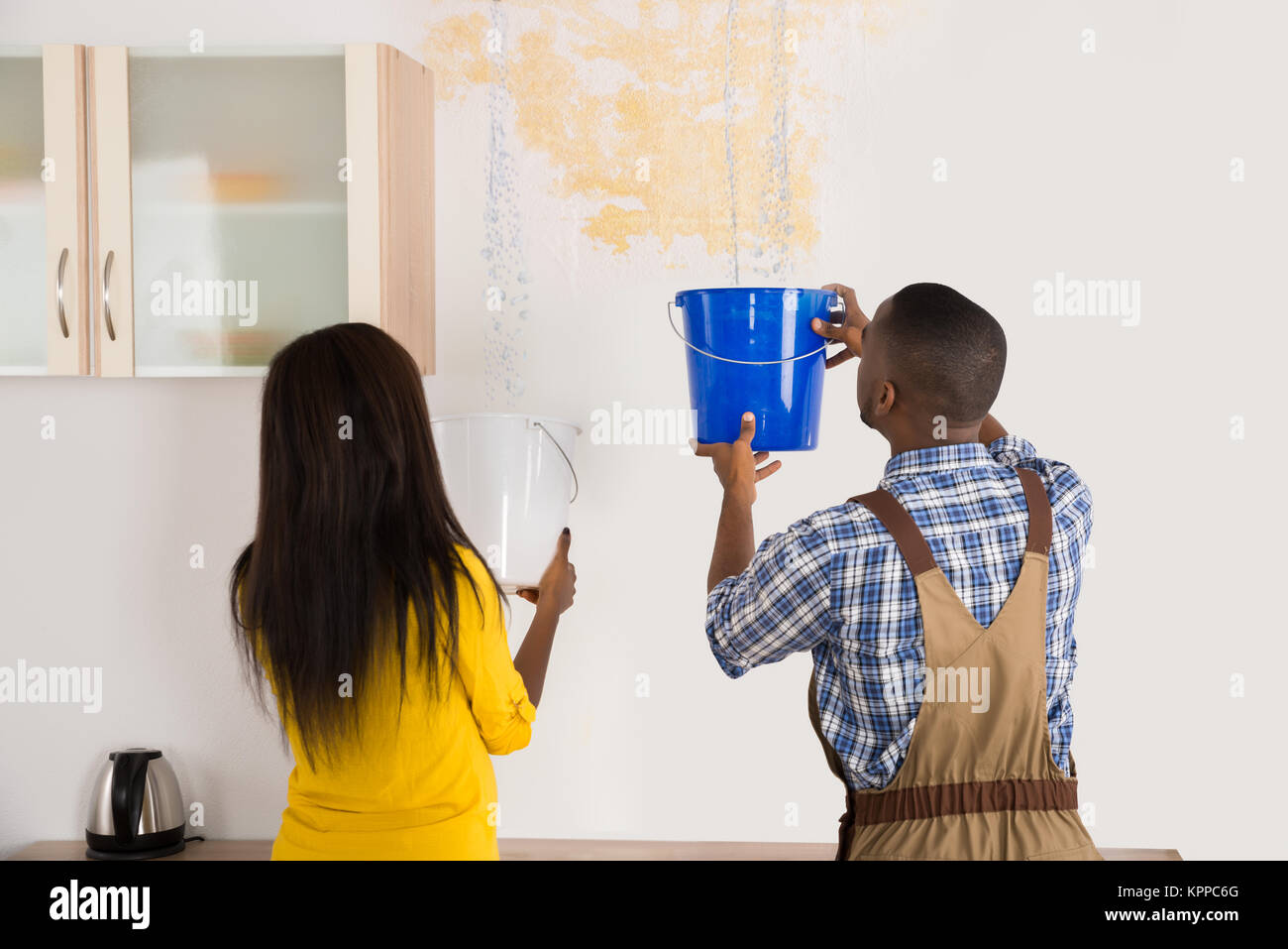 Young Woman And Worker Collecting Water In Bucket From Ceiling - Stock Image