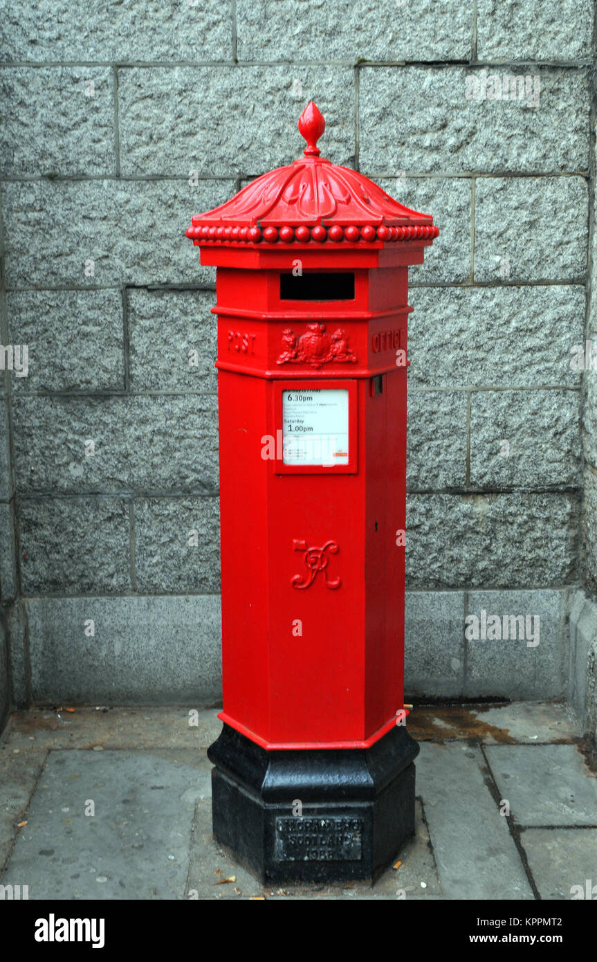 A traditional red pillar box operated by the Royal Mail with a finial on the top and ornately designed cast iron - Stock Image