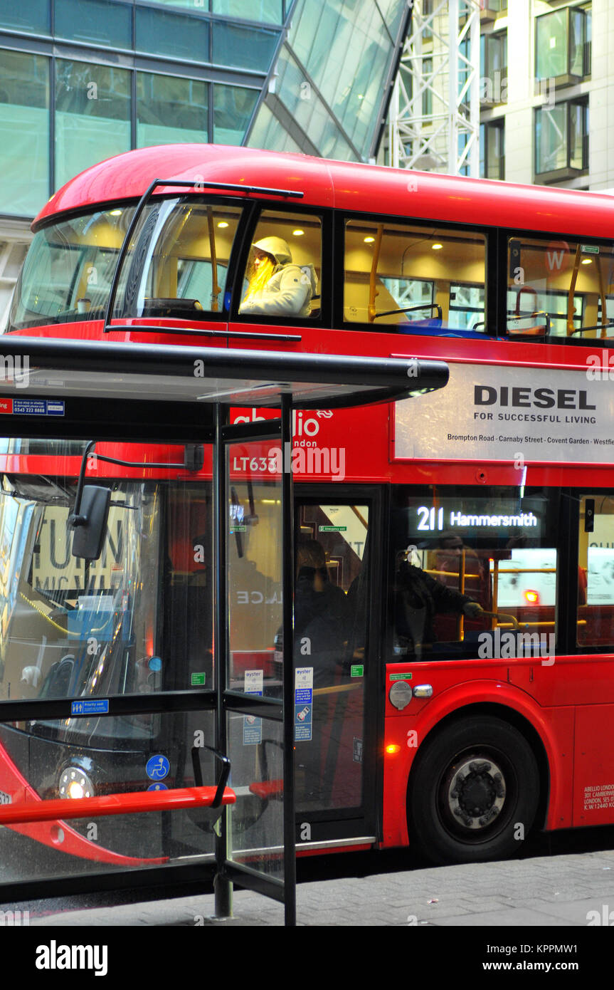 A new style red routemaster london bus working in centre of the city taking commuters to work and shoppers to the - Stock Image