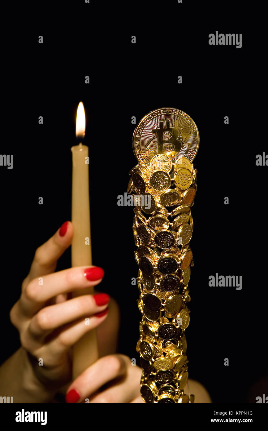 Female hands hold a candle in front of bitkoin. - Stock Image