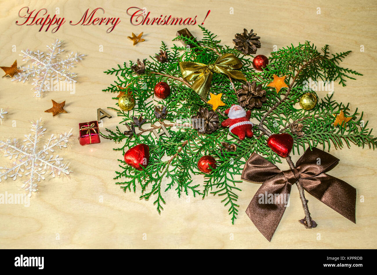 Toy Santa Claus,chocolate balls and hearts,cones and satin bows with snowflakes and Happy Merry Christmas  on the - Stock Image